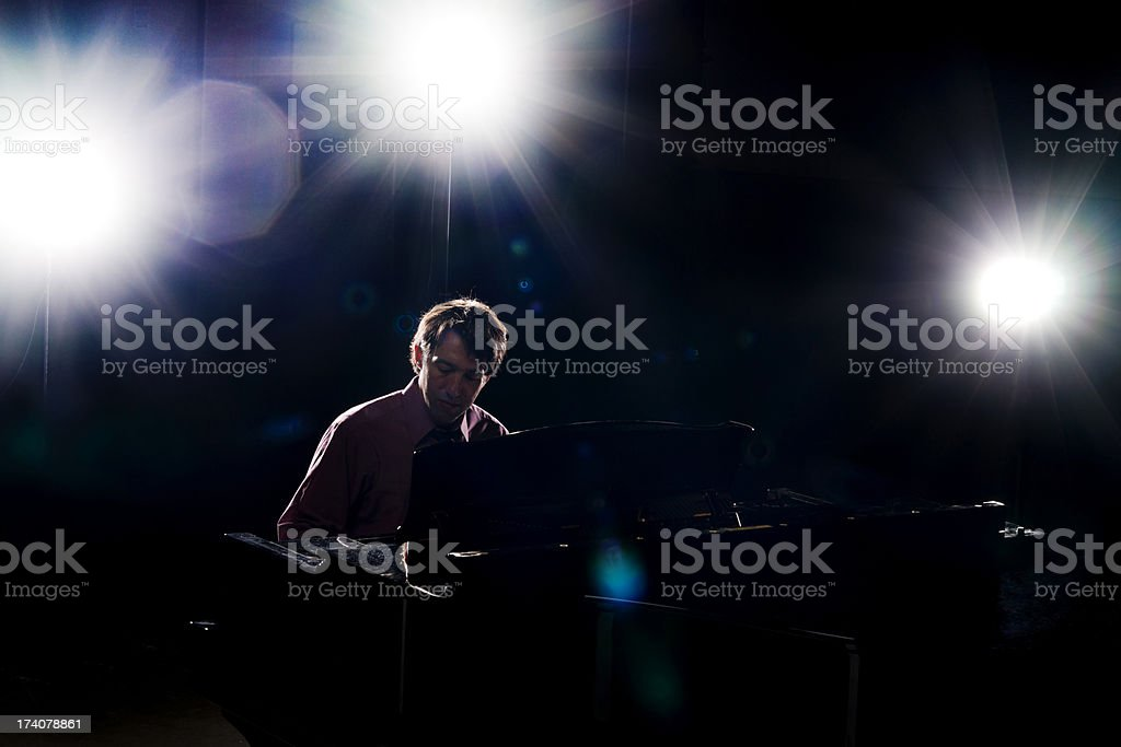Stock photo of a man in his thirties playing a piano on stage.