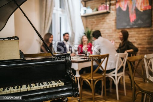 Piano in restaurant where group of friends having dinner