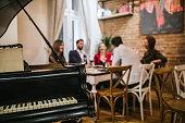 Piano in restaurant where group of friends having dinner