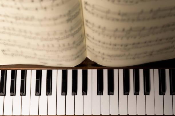 klaviertastatur und filmmusik - piano noten stock-fotos und bilder