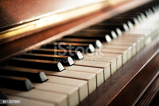 Piano keyboard of an old music instrument, close up with blurry background, selective focus and very narrow depth of field
