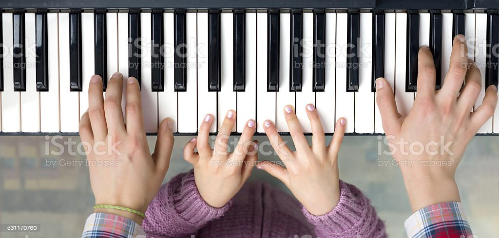 Piano Keyboard top View and Hands of Child and Mother stock photo