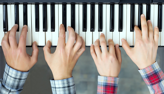Piano Keyboard top View Hands of Man and Woman playing
