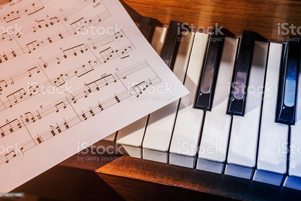 Piano keys and sheet music stock photo