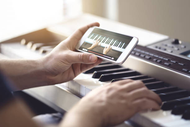Piano lesson online. Man watching video tutorial with mobile phone and practising playing. Person learning to play an instrument with an internet course and class. stock photo