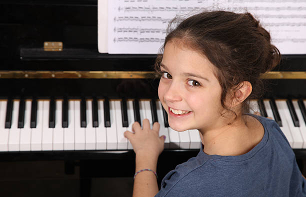 Piano lesson Young girl seated in front of a piano keyboard pianist stock pictures, royalty-free photos & images