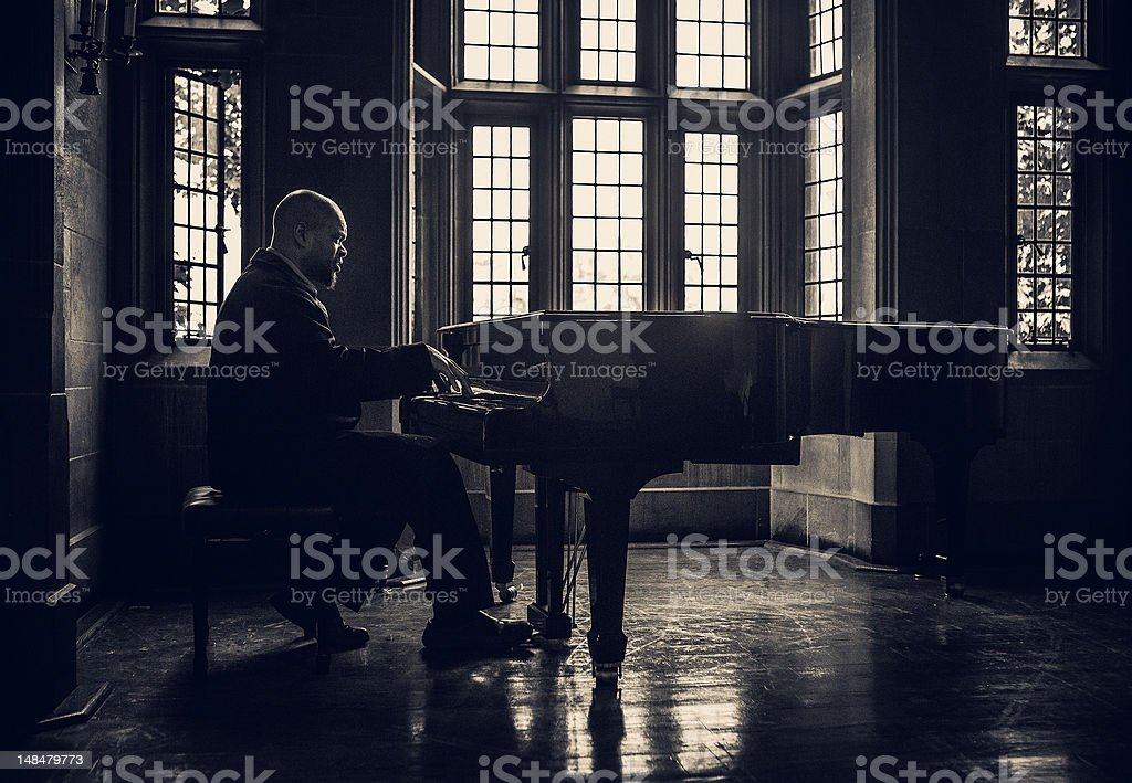 african american man performing on a classic piano, old room with...