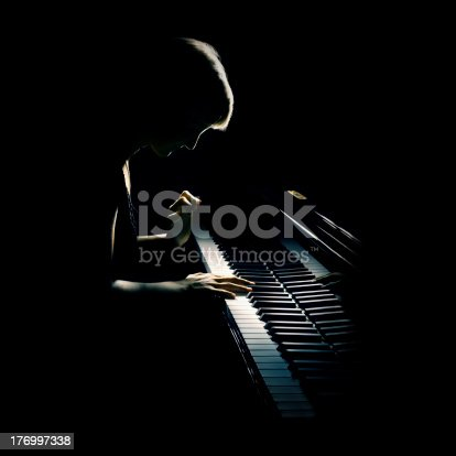 Piano playing pianist concert. Classical musician player with grand piano in darkness