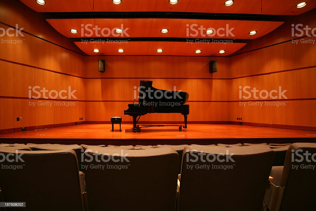 Piano sitting in the middle of the stage in an auditorium stock photo