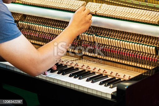 Piano technician  is checking the piano for the customer.Internal parts of the piano