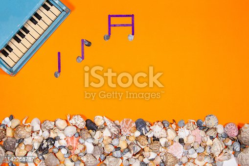 Piano toy and melody notes. Concept Image on orange color background with seashells