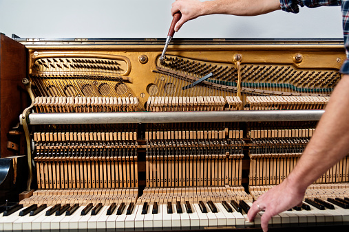 Colour photo of a piano tuner at work tuning an upright piano. Horizontal format showing the complicated internal workings of a piano, with one hand the man is using a ratchet to tighten or loosen the correct wire to tune the key his other hand is pressing.
