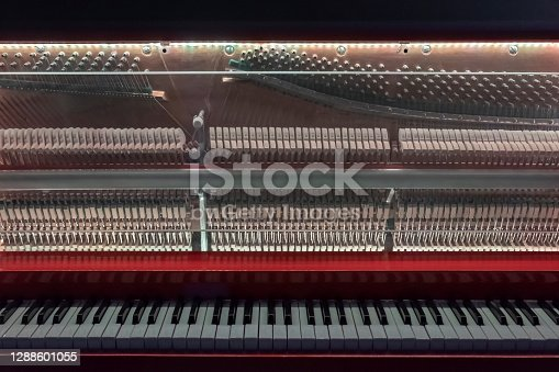 Piano with glass front cover. Piano keys and piano inside. Piano interior detail.