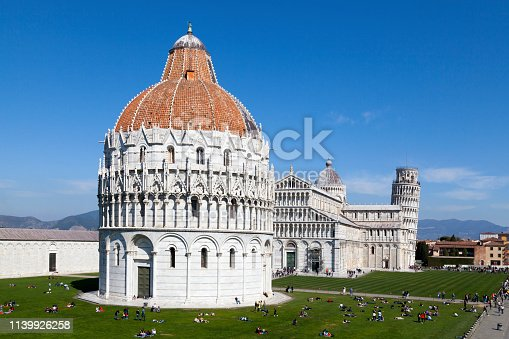Pisa, Italy - March 31 2019: The Piazza dei Miracoli (English: Square of Miracles), formally known as Piazza del Duomo (English: Cathedral Square), is recognized as an important centre of European medieval art and one of the finest architectural complexes in the world.