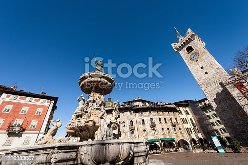 Trento, Trentino Alto Adige, Italy - March 8th, 2020: Piazza del Duomo, Cathedral square in Trento city with the Neptune fountain, Civic tower (Torre Civica), Praetorian Palace (Palazzo Pretorio or Palazzo Vescovile) and the frescoed houses Cazuffi Rella, XVI century. A group of people are sitting under the arcades of a cafeteria overlooking the square