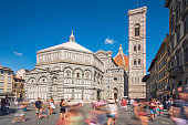A crowded summer day with people in motion at Piazza del Duomo in Florence, Italy.