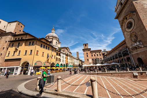 Mantua, Italy - May 9th, 2021: Piazza delle Erbe (square of herbs), in Mantua downtown with the Basilica and Cathedral of Sant'Andrea (Saint Andrew, 1472-1732) and the medieval Palazzo della Ragione (Palace of the Reason, XI-XII century) with the clock tower. Lombardy, Italy, Europe. A large group of tourists and locals stroll through the historic center or have lunch sitting in one of the many restaurants on a sunny spring day.