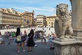 Tourists at Piazza di Santa Croce, a city square in central Florence, Italy. On the right stands a sculpture of a lion with a shield, a symbol of Florence and Tuscany (known as Marzocco).