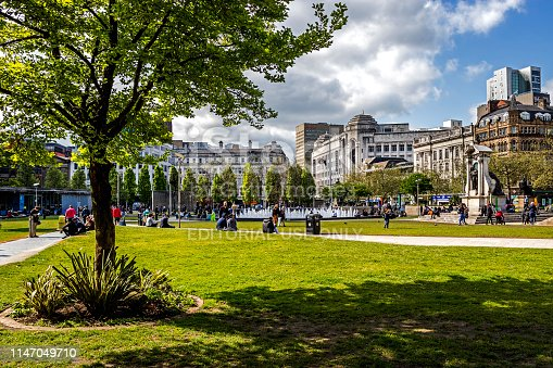 View across Piccadilly Gardens in the centre of Manchester, UK.  Shops and buildings can be seen in the distance and people can be seen walking and sitting in the gardens.