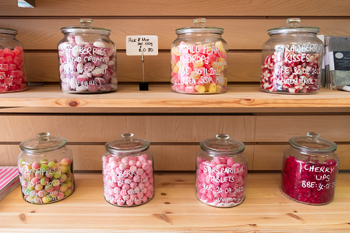 A selection of sweets in clear glass jars on a shelf in a plastic free store.