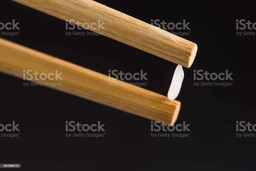 Pick up Rice with chopsticks in black background stock photo
