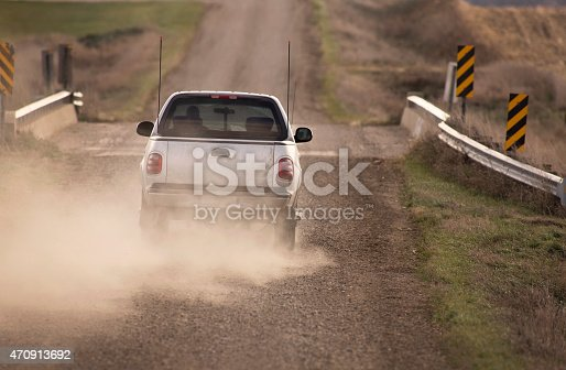A silver pick up truck travels down a dusty rural midwestern road creating a plume of dust behind it. Truck is approaching a small bridge bordered by farmland on either side.