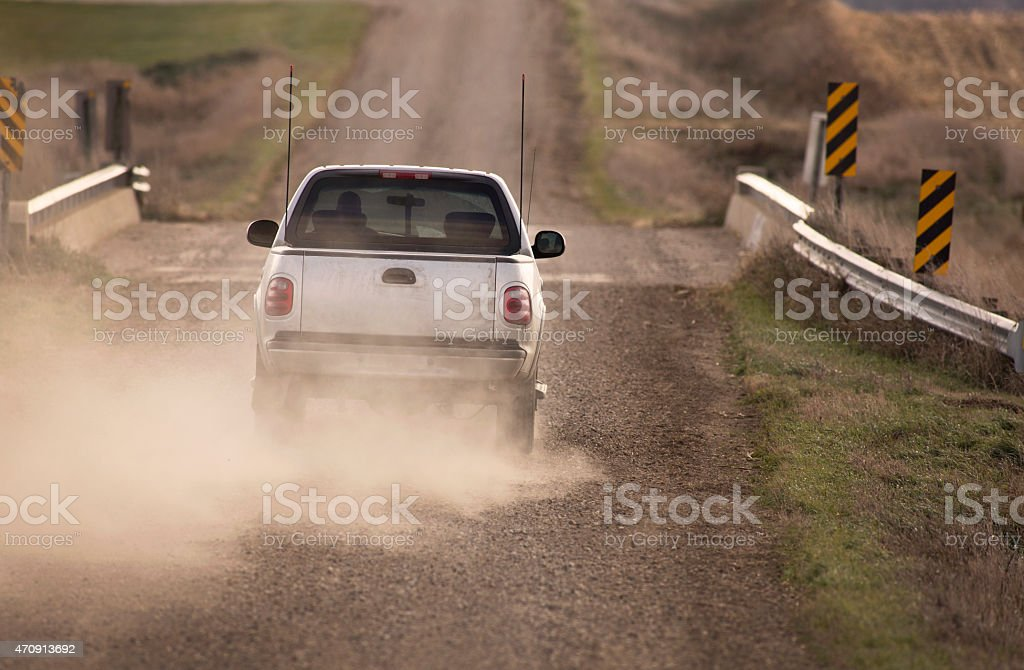 Pick Up Truck Traveling Down Dusty Rural Road. stock photo