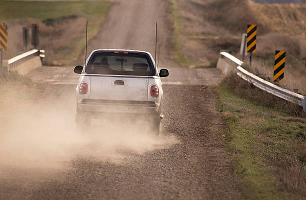 Pick Up Truck Traveling Down Dusty Rural Road.