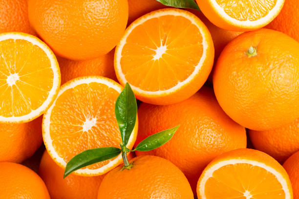 Picked orange fruits. Fresh orange fruits with green leaves as background. orange fruit stock pictures, royalty-free photos & images