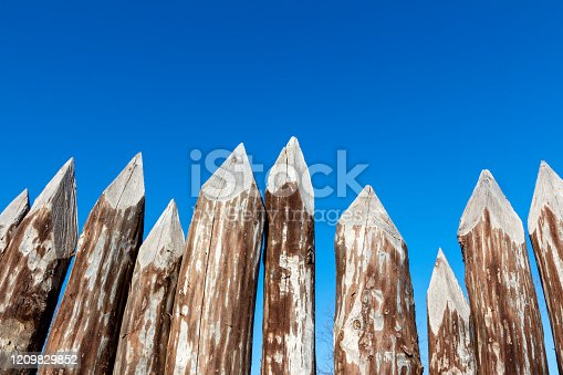Palisade or fence of thick round tree trunks with a pointed top against a blue sky