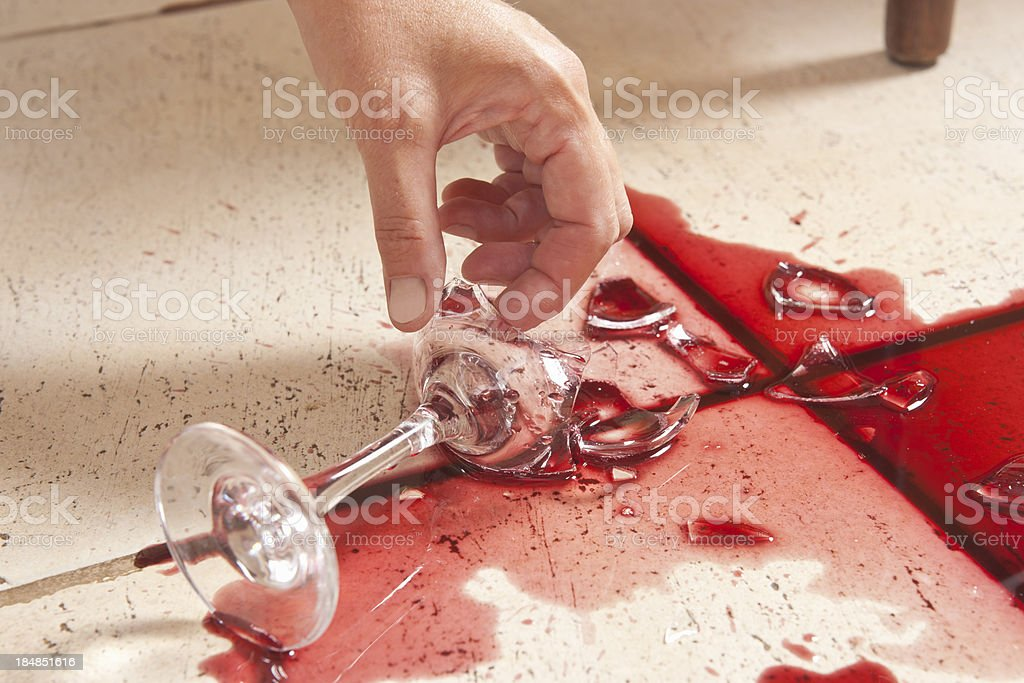 Picking a broken wine glass with bare hands stock photo