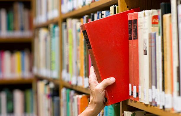 女性の手摘みのご予約は、濃赤色テキストライブラリからの保管 - 図書館 ストックフォトと画像
