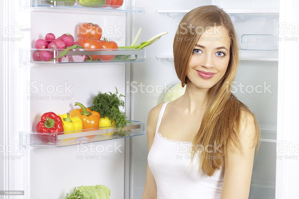 Picking food from fridge. Vegetables in the refrigerator royalty-free stock photo