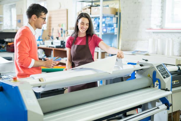 Picking out color for printing Cheerful excited beautiful lady in apron showing printed banner to manager who picking out color on swatch for printing printing plant stock pictures, royalty-free photos & images