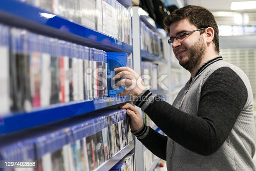 Profile of a handsome young guy browsing the gaming section at a local store