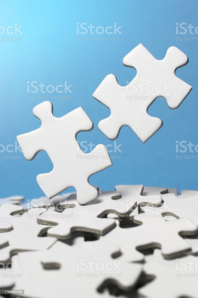 Picking out two fitting puzzle pieces.(vertical) royalty-free stock photo