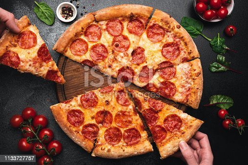 Picking slice of pepperoni pizza. Hands picking pizza slice. Top view of tasty hot pepperoni pizza on black concrete background