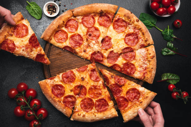 Picking slice of pepperoni pizza Picking slice of pepperoni pizza. Hands picking pizza slice. Top view of tasty hot pepperoni pizza on black concrete background pizza stock pictures, royalty-free photos & images