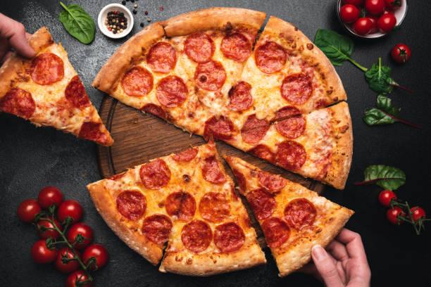 pepperoni pizza çekme dilimi - i̇talyan mutfağı stok fotoğraflar ve resimler