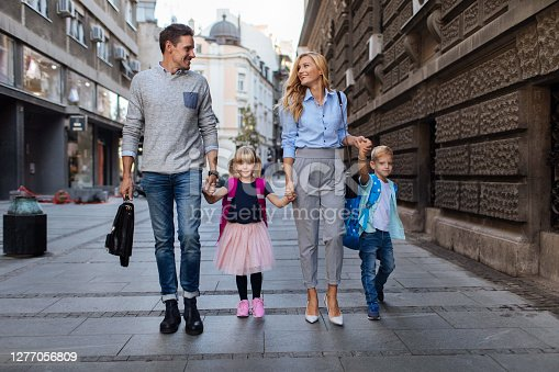 Portrait shot of a young couple walking around town with their kids