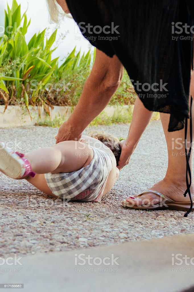 Picking up a baby girl from the ground stock photo