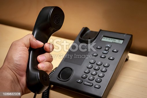 Picking up a phone call from a black telephone