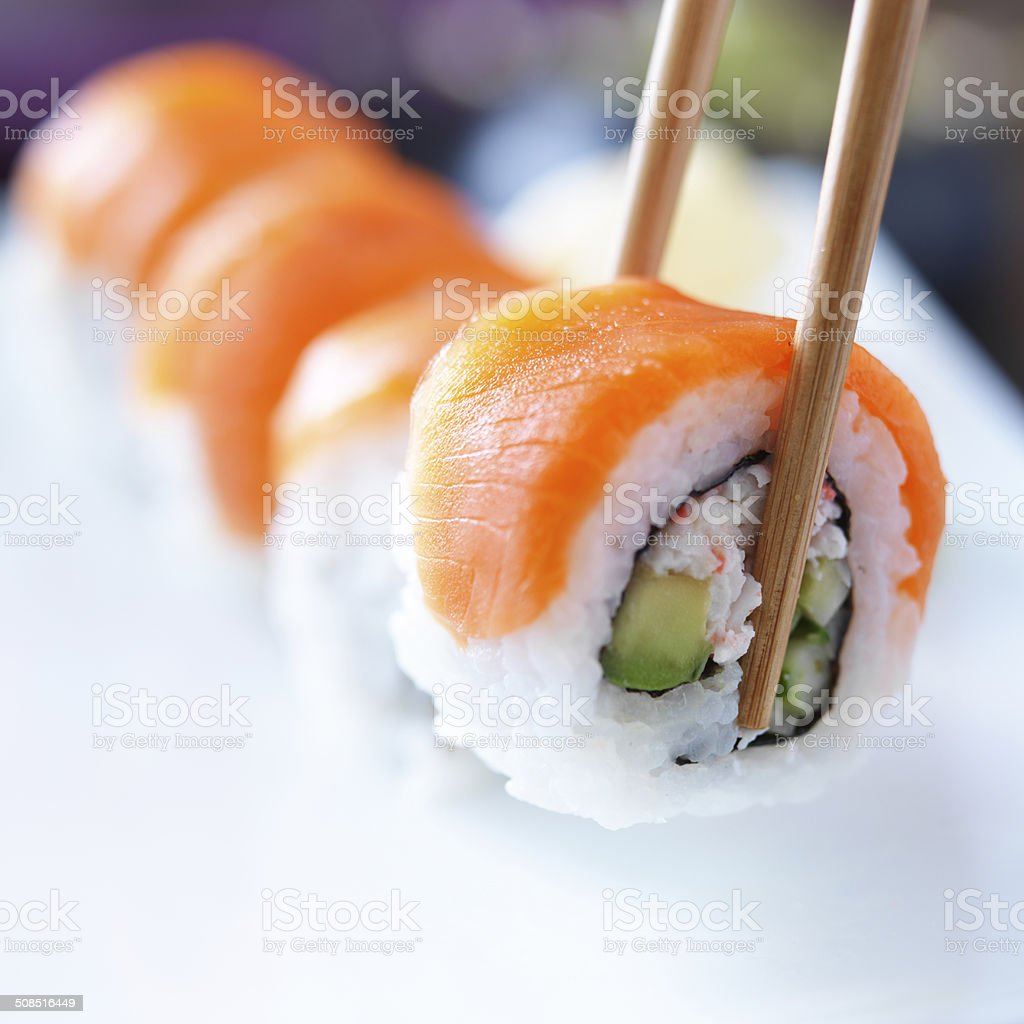 picking up a piece of sushi with chopsticks stock photo
