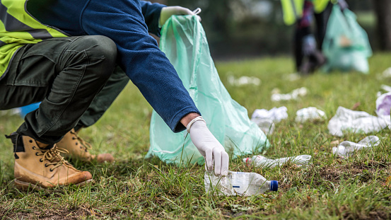 Unrecognizable volunteer picking up a plastic bottle during a park clean-up action.