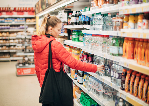 A young woman picks up a bottle of water in the supermarket.