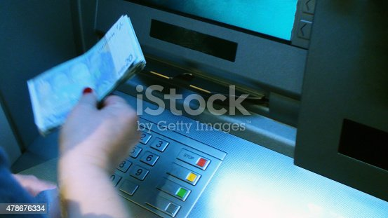 istock Picking Up Some Money From ATM Cash Withdrawal Machine 478676334