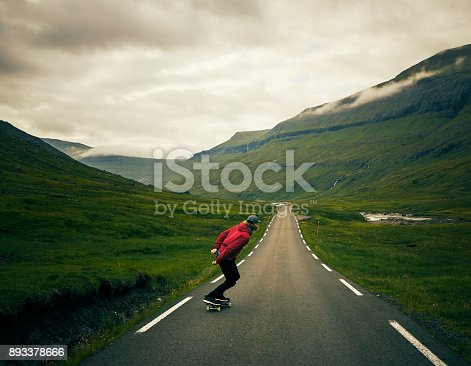 Rearview shot of an unrecognizable young man riding down a road with a skateboard outside in a rural area