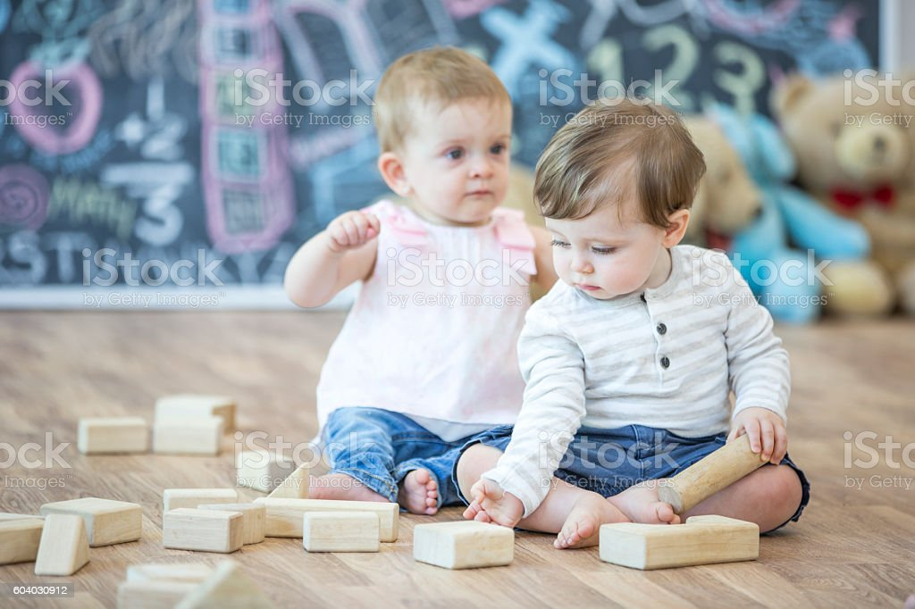 Babies play together in a daycare. They play with blocks and share...
