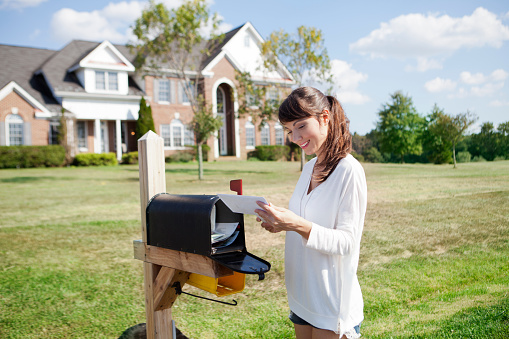 Beautiful american housewife checking mail box