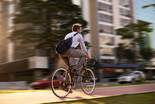 Shot of an attractive young man on his morning bicycle commute to work